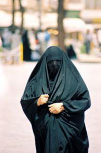 Una dona camina per un carrer de l'Afganistan amb la cara tapada.